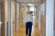 canvas print picture - portrait of elderly woman walking down hallway in retirement home background