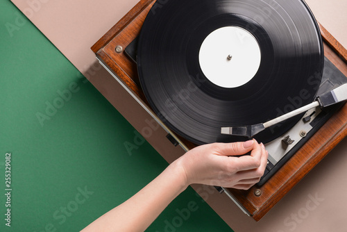 Hand of woman switching on record player with vinyl disc Fototapeta