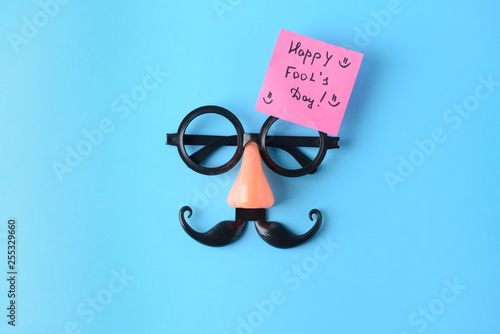 Fotografía  Party decor and sticky note with text HAPPY FOOL'S DAY on color background