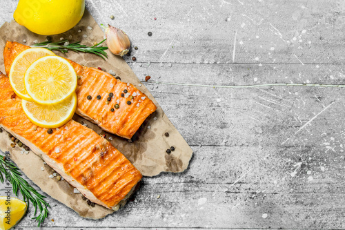 Fotografija Grilled salmon fillet with slices of fresh lemon.