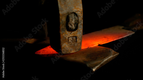 Tablou Canvas MACRO, DOF: Stunning shot of hot piece of metal held by tongs and hit by hammer