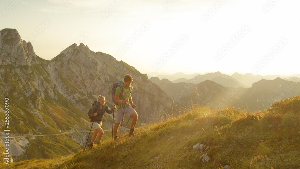 Fototapety, obrazy: LENS FLARE: Golden sunbeams shine on active couple trekking up the grassy hill.