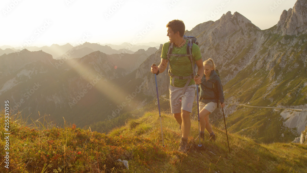 Fototapety, obrazy: SUN FLARE Carefree man and girlfriend explore the beautiful golden lit mountains