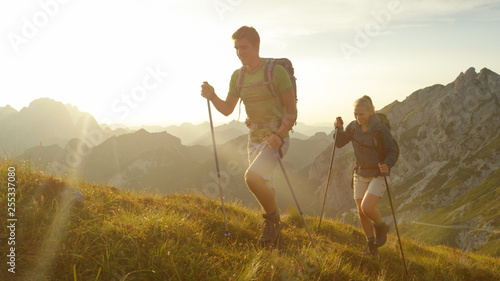 Fotografia SUN FLARE: Happy woman and man enjoying a morning hike in the stunning mountains