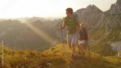 Fototapeta SUN FLARE Carefree man and girlfriend explore the beautiful golden lit mountains obraz