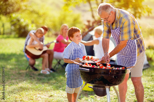 Obraz smiling grandfather giving grandson grilling meat. - fototapety do salonu