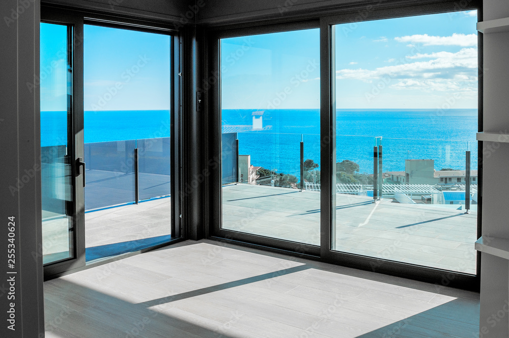 Fototapety, obrazy: Empty rooms in a new house with large windows overlooking the sea. Automatic blinds. Glass partition terrace.