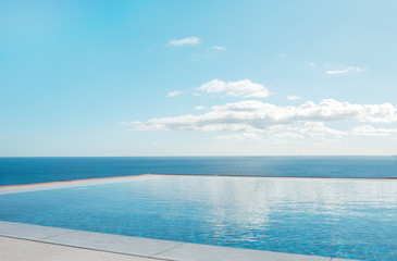 Fototapeta na wymiar Luxury swimming pool in front of the sea. Swimming pool with beautiful sea and sky view.
