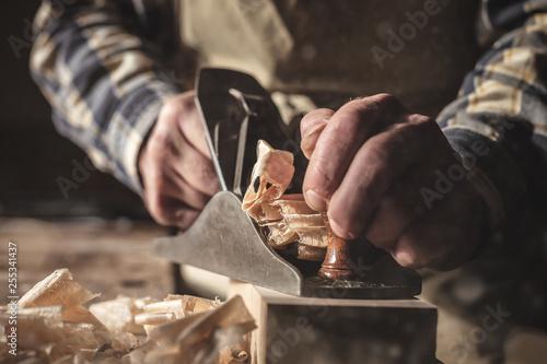 Obraz Hände eines Schreiners bei der Arbeit mit dem Hobel - fototapety do salonu