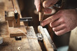 Hände eines Instrumentenbauers setzen einen Keil in den Geigenfrosch
