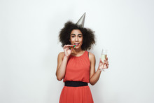 Cheers! Attractive Young Afro American Women In Dress And Party Hat Holding A Glass With Champagne And Blowing Party Whistle
