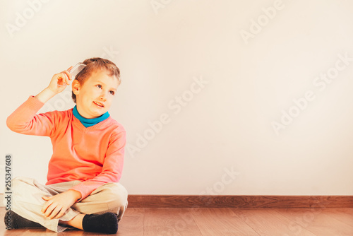 Fototapeta Child sitting on the floor of his house looking handsome while he only combs his hair, concept of independent and autonomous child. obraz na płótnie