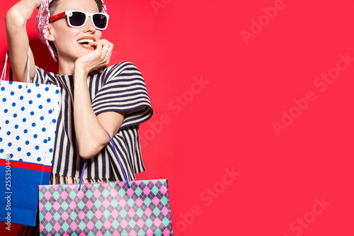Fotografía  Happy shopping woman with shopping bags over bright red background wearing hat a