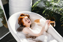 Joyful Beautiful Caucasian Woman With Redhead Hair Knot Wrapped In Bath Towel Singing Dramatically Using Brush As Microphone Relaxing In Bath Full Of Foam In The Spacious Bathroom.