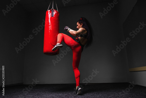 Fotografia, Obraz Kickboxing young woman punching kicking the bag