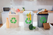 Waste sorting at home. Protect the environment. Colorful garbage bins with recycling icon full of plastic, food, paper on the table close-up