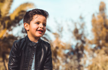 Fashion Little Boy Wearing A Leather Jacket. Park Or Forest, Outdoor