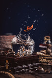 Water splash and orange paper boat in round glass on wooden box with seashells and marine rope. Highspeed photography, dark, copy space.