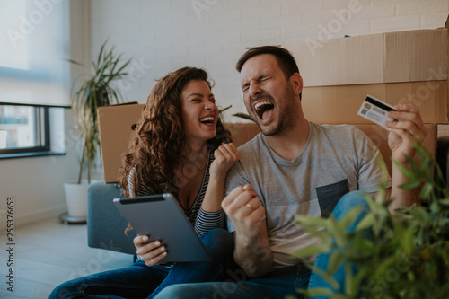 500556805a Online shopping makes life easier. Smiling young couple sitting on the floor  of their new