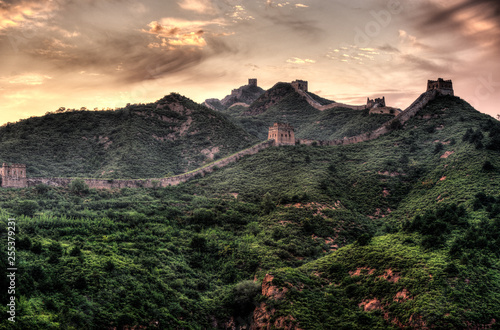 Fotografie, Obraz Great Wall of China and beautiful mountains covered by forest in dramatic light