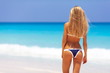 Leinwanddruck Bild - Travel vacation wallpaper - Beautiful young pretty blonde girl in bikini with white sand on perfect sport sexy body relax in sea of white sand paradise tropical Maldive Seychelles beach on resort