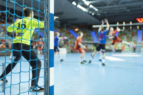 Detail of handball goal post with net and handball match in the background Fototapet