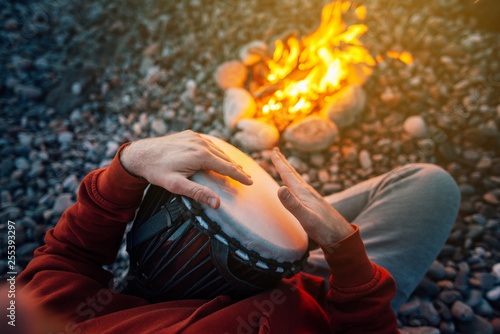 Fotografia, Obraz percussionist playing djembe sitting by fire, close-up