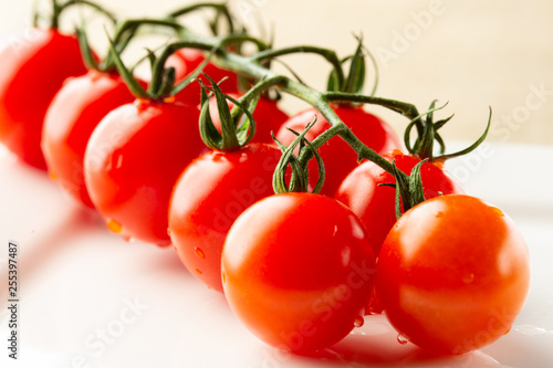 Fotografía  Raw of ripe red tomatoes on the branch with drops of water