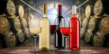 Collection Of Equisite Red White And Rose Wine Bottle Glasseson Wooden Table  In Front Of Old Rustic Winery Cellar Background