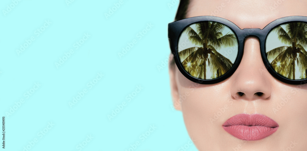 Fototapety, obrazy: Portrait close up of a pretty woman with reflection of palms in sunglasses  on a bright background