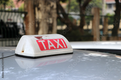 Fotografía  Broken Taxi light sign or cab sign in white and red color with white text on the car roof at the street blurred background