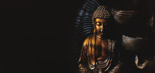 Golden Gautama Buddha Statue With A Black Background.