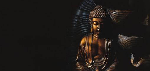 Zlatni kip Bude Gautama s crnom pozadinom.