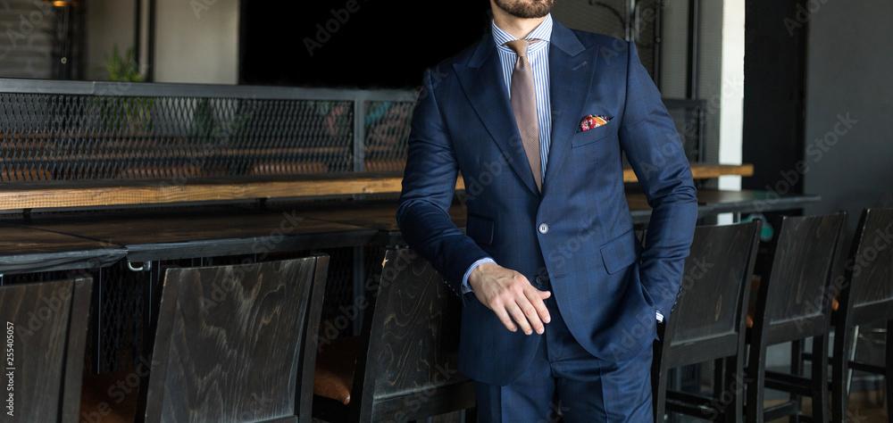 Fototapeta Man in expensive custom tailored suit standing an posing indoors