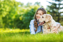 Young Woman With Golden Retriever Dog In The Summer Park