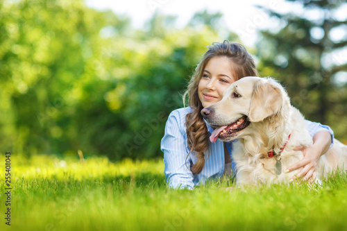 Fotografia Young woman with golden retriever dog in the summer park