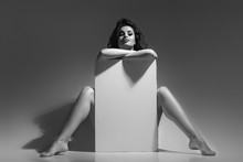 Sexy Naked Brunette Woman Sitting And Holding Empty Board. Attractive Girl With Blank Board With Copy Space Looking At Camera. Black And White