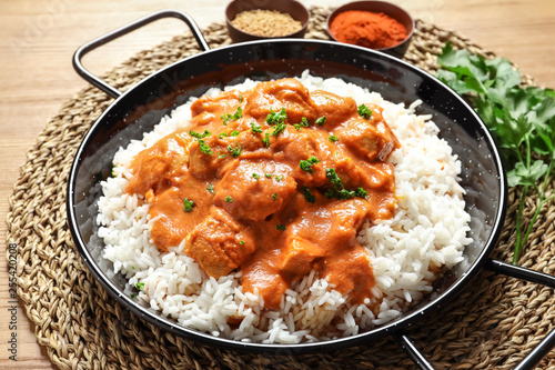 Delicious butter chicken with rice in dish on wooden table Canvas Print