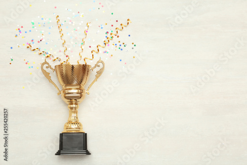 Fotografía  Golden trophy cup and streamers on wooden background, top view with space for te