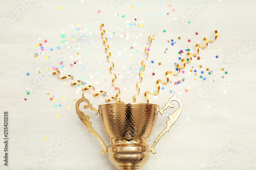 Golden trophy cup and streamers on wooden background, top view Fototapet