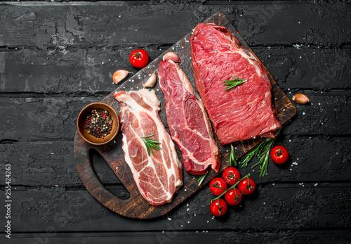 Fototapeta Raw meat. Beef and pork steaks with spices on the cutting Board. obraz na płótnie