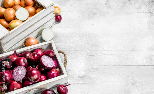 Fototapeta Yellow onions in the box and red onions on the tray. obraz