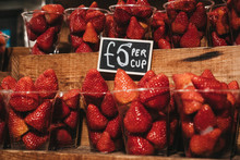 Cups Of Fresh Strawberries On Sale, Portioned In Plastic Cups, On Top Of A Wooden Shelves.