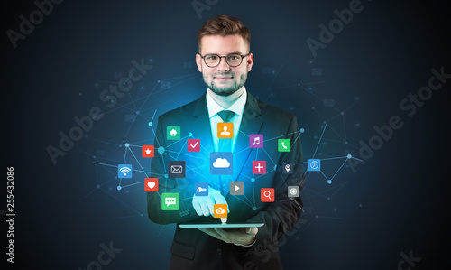 Fényképezés  Handsome businessman in suit with tablet on his hand and application icons above