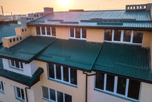 Aerial View Of Attic Annex Room Exterior With Plastic Windows, Roof And Walls Covered With Green Metal Siding Planks, New Gutter System On Top Of High Multi-storey Apartment Building.