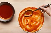 Man Spreading Tomato Paste On Pizza Base