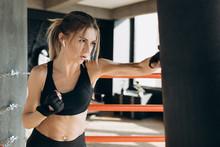 Female Punching A Boxing Bag W...