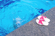 Summer background with white-pink slippers for the pool, near the pool