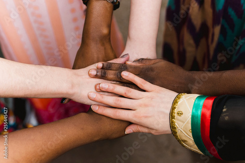 Fototapeta National diversity. People of different appearance and nationality stand in a circle together and hold hands. Team building and partnership business concept obraz