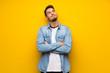 Leinwandbild Motiv Handsome man over yellow wall looking up while smiling